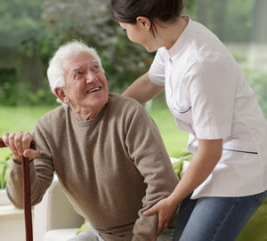 Elderly man with cane being helped by physician